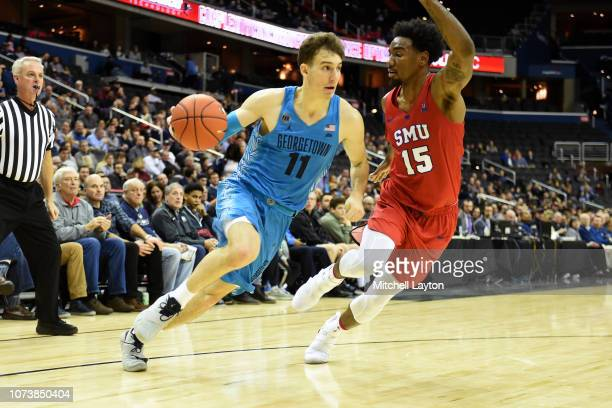 Greg Malinowski of the Georgetown Hoyas dribbles around Isiaha Mike of the Southern Methodist Mustangs during a college basketball game at the...