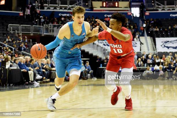 Greg Malinowski of the Georgetown Hoyas dribbles around Jarrey Foster of the Southern Methodist Mustangs during a college basketball game at the...