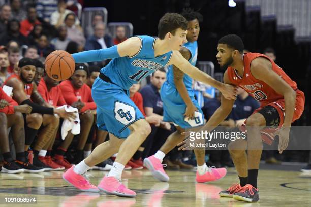 Greg Malinowski of the Georgetown Hoyas dribbles around LJ Figueroa of the St John's Red Storm during a college basketball game at the Capital One...