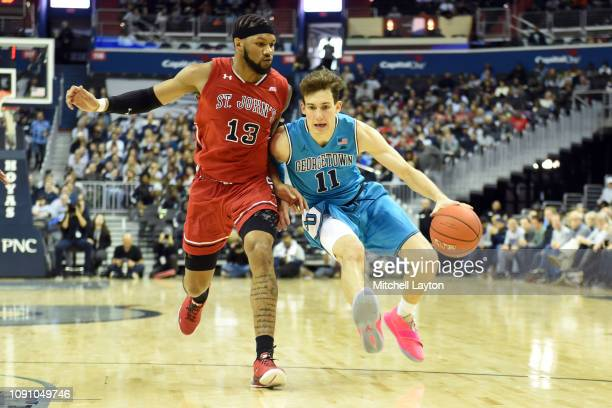 Greg Malinowski of the Georgetown Hoyas dribbles by Marvin Clark II of the St John's Red Storm during a college basketball game at the Capital One...