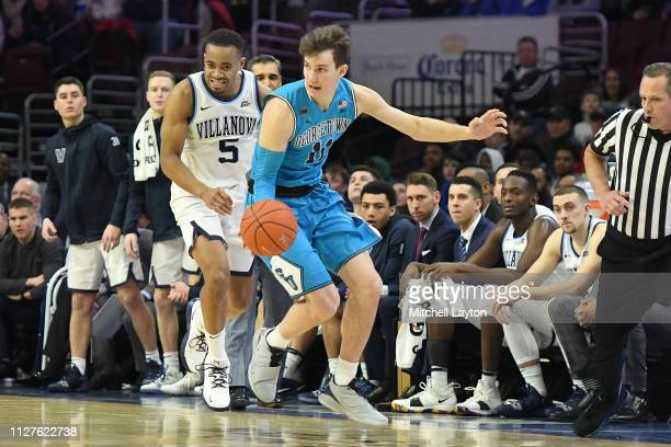 Greg Malinowski of the Georgetown Hoyas dribbles the ball by Phil Booth of the Villanova Wildcats during a college basketball game at the Wells Fargo...