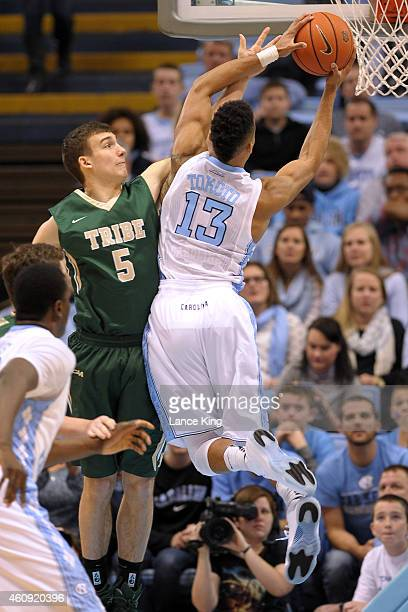 Greg Malinowski of the William Mary Tribe defends a shot by JP Tokoto of the North Carolina Tar Heels during their game at the Dean Smith Center on...