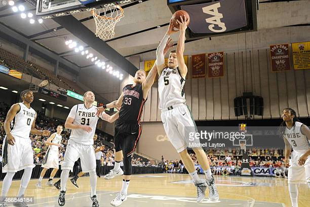 Greg Malinowski of the William Mary Tribe pulls down a rebound over Zach Stahl of the Northeastern Huskies during the Championship of the CAA...