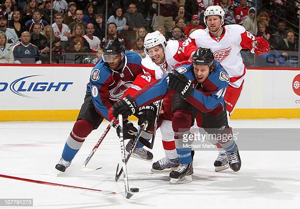 Greg Mauldin and Ryan Wilson of the Colorado Avalanche reach for the puck around defender Brad Stuart of the Detroit Red Wings at the Pepsi Center on...