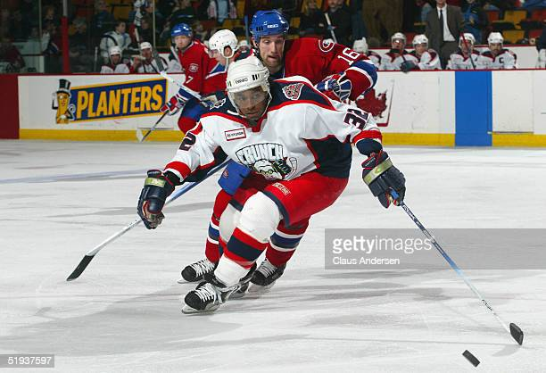 Greg Mauldin of the Syracuse Crunch skates under pressure from Jason Ward of the Hamilton Bulldogs during the American Hockey League game at Copps...