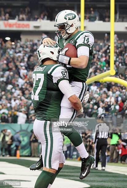 Greg McElroy of the New York Jets celebrates after throwing a touchdown pass in the fourth quarter against the Arizona Cardinals with teammate Konrad...
