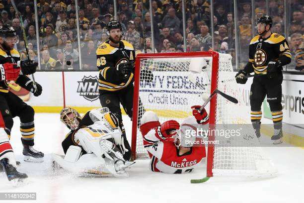 Greg McKegg of the Carolina Hurricanes falls into the net after scoring a goal against Tuukka Rask of the Boston Bruins during the second period in...