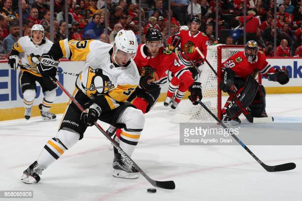 Greg McKegg of the Pittsburgh Penguins and Jan Rutta of the Chicago Blackhawks chase the puck in the first period at the United Center on October 5...