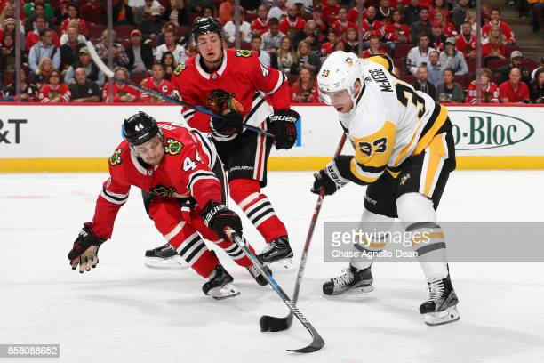 Greg McKegg of the Pittsburgh Penguins and Jan Rutta of the Chicago Blackhawks battle for the puck as John Hayden watches in the third period at the...