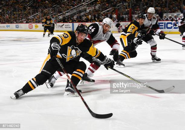 Greg McKegg of the Pittsburgh Penguins moves the puck in front of Kevin Connauton of the Arizona Coyotes at PPG Paints Arena on November 7 2017 in...