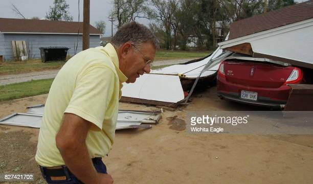 Greg Miller looks over the remains of his garage and car Monday afternoon Aug 7 2017 in Kiowa Kan Miller was parked in the drive in his truck ready...