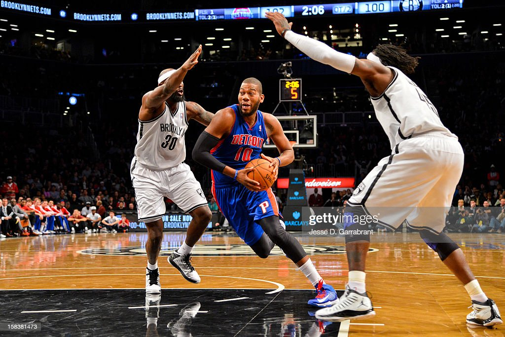 Greg Monroe #10 of the Detroit Pistons drives against Reggie Evans #30 and Gerald Wallace #45 of the Brooklyn Nets at the Barclays Center on December 14, 2012 in the Brooklyn borough of New York City.