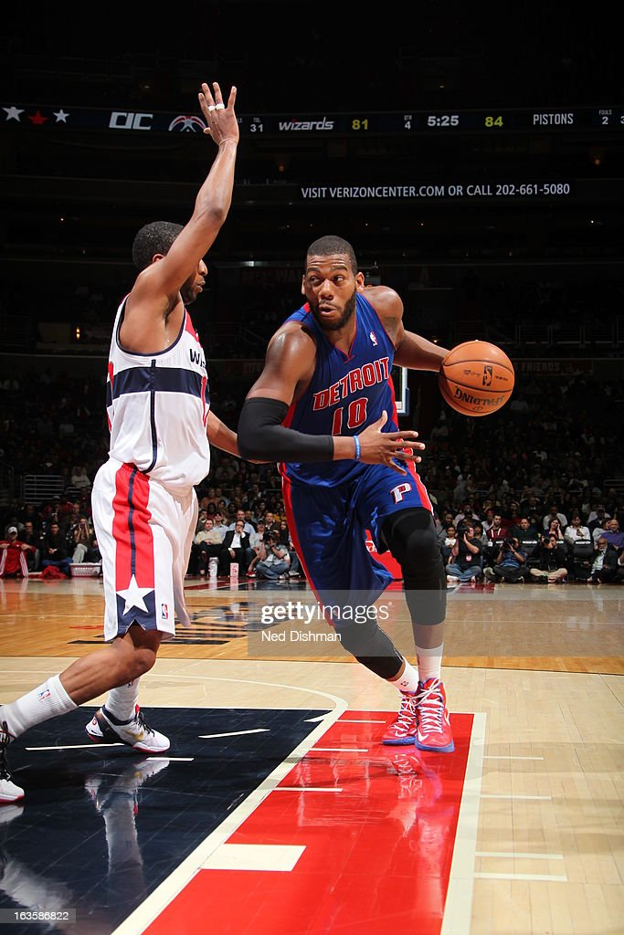 Greg Monroe #10 of the Detroit Pistons drives to the basket against A.J. Price #12 of the Washington Wizards at the Verizon Center on February 27, 2013 in Washington, DC.