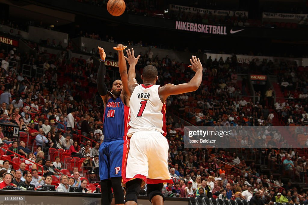 Greg Monroe #10 of the Detroit Pistons shoots against Chris Bosh #1 of the Miami Heat on March 22, 2013 at American Airlines Arena in Miami, Florida.