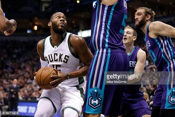 Greg Monroe of the Milwaukee Bucks draws the foul on Roy Hibbert of the Charlotte Hornets during the first quarter at BMO Harris Bradley Center on...