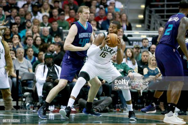 Greg Monroe of the Milwaukee Bucks dribbles the ball while being guarded by Cody Zeller of the Charlotte Hornets in the fourth quarter at BMO Harris...