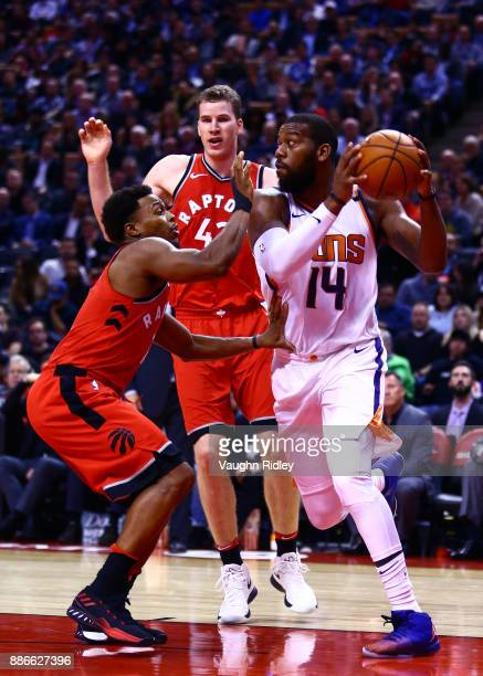 Greg Monroe of the Phoenix Suns dribbles the ball as Kyle Lowry and Jakob Poeltl of the Toronto Raptors defends during the second half of an NBA game...