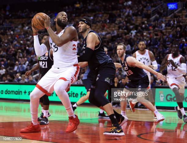 Greg Monroe of the Toronto Raptors shoots the ball as Josh Boone of Melbourne United defends during the second half of an NBA preseason game at...