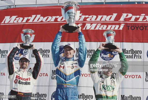Greg Moore of Canada driver of the Player's Forsythe Racing Reynard 99i Mercedes hold aloft the trophy and celebrates with second placed Michael...