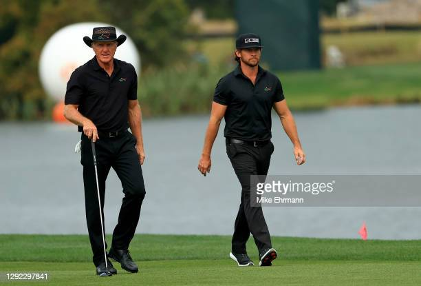 Greg Norman and son Greg Norman Jr. Walk up the 18th hole during the final round of the PNC Championship at the Ritz Carlton Golf Club on December...