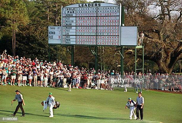 Greg Norman of Australia and Nick Faldo of England walk to the eighteenth green past the leaderboard during final round action of The Masters at...