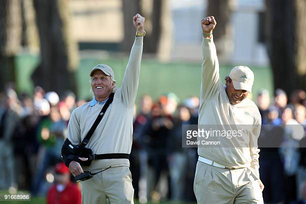 Greg Norman of Australia and the captain of the International Team celebrates with Angel Cabrera of Argentina as Tim Clark holes an eagle putt to win...