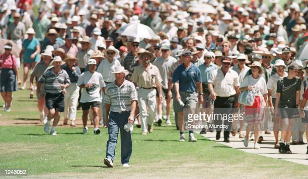 Greg Norman of Australia is followed by a large crowd as he walks down the fairway on the third hole during the first round at the 1996 Heineken...