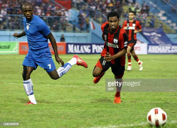 Greg Nwokolo of Arema Indonesia and Imanuel Wanggai of Persipura Jayapura go for the ball during the Inter Island Cup tournament under the control of...