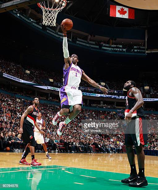 Greg Oden of the Portland Trail Blazers looks on as Amar'e Stoudemire of the Phoenix Suns goes in for a layup during their preseason game at General...