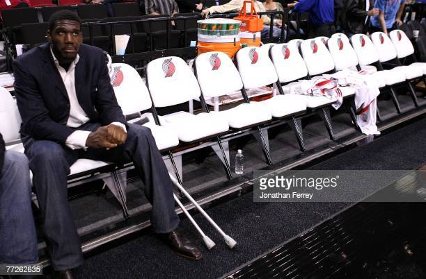 Greg Oden of the Portland Trail Blazers who is out for the season after under going micro fracture surgery in his knee sits on the bench to watch a...