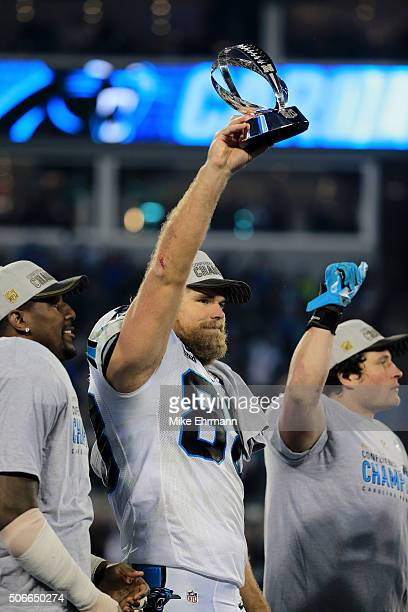 Greg Olsen of the Carolina Panthers holds the George Halas Trophy after defeating the Arizona Cardinals with a score of 49 to 15 to win the NFC...