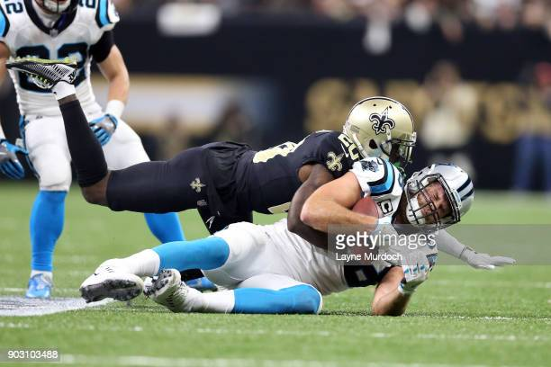 Greg Olsen of the Carolina Panthers is tackled by Ken Crawley of the New Orleans Saints during the first half of the NFC Wild Card playoff game at...