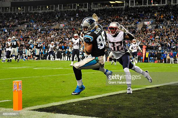 Greg Olsen of the Carolina Panthers makes a touchdown catch as Devin McCourty of the New England Patriots defends during play at Bank of America...