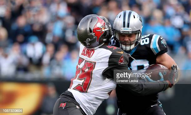 Greg Olsen of the Carolina Panthers runs the ball against Devante Bond of the Tampa Bay Buccaneers in the fourth quarter during their game at Bank of...