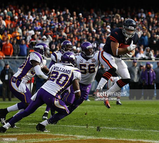 Greg Olsen of the Chicago Bears catches a touchdown pass over EJ Henderson and Madieu Williams of the Minnesota Vikings at Soldier Field on November...