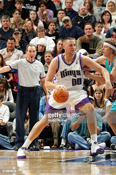 Greg Ostertag of the Sacramento Kings dribbles the ball against Chris Andersen of the New Orleans Hornets on December 19 2004 at Arco Arena in...