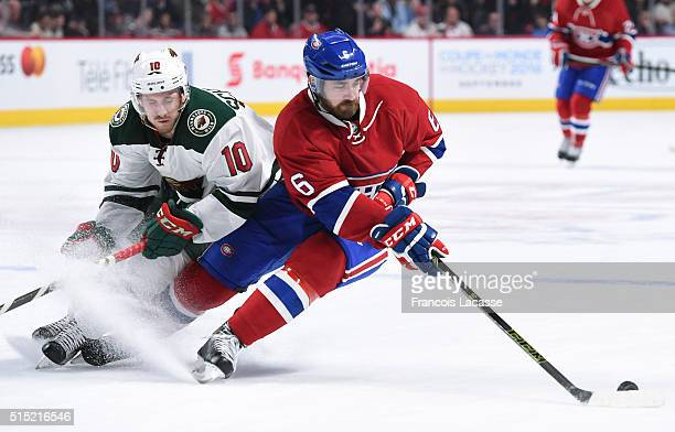 Greg Pateryn of the Montreal Canadiens controls the puck while being challenged by Jordan Schroeder of the Minnesota Wild in the NHL game at the Bell...
