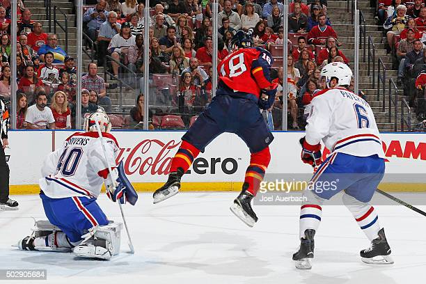 Greg Pateryn of the Montreal Canadiens looks on as Reilly Smith of the Florida Panthers jumps up to let the puck go towards goaltender Ben Scrivens...