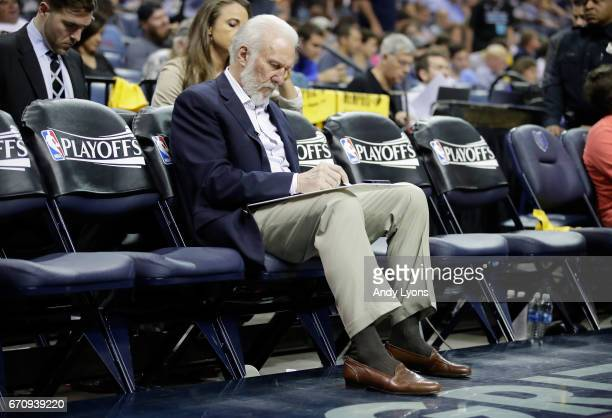 Greg Popovich the head coach of the San Antonio Spurs draws up a play while on the bench against the Memphis Grizzlies in game three of the Western...