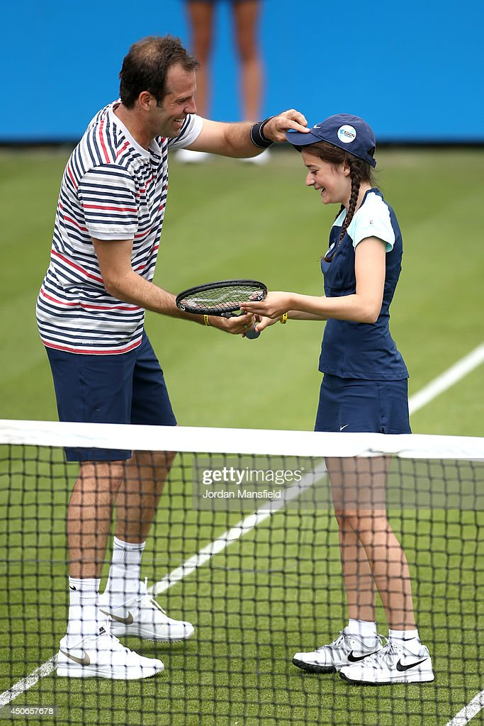 Greg Rusedski of Great Britain gives a hat and a racket to a ball-girl during the Rally for Bally exhibtion match against Colin Fleming of Great Britain and Agnieszka Radwanska of Poland on day two of the Aegon International at Devonshire Park on June 15, 2014 in Eastbourne, England.