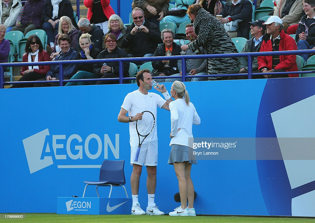 Greg Rusedski of Great Britain takes a glass of wine from a spectator partnering Lindsay Davenport of USA (not in picture) in their mixed doubles exhibition legends match against Mark Philippoussis and Rennae Stubbs (R) of Australia during day two of the AEGON International tennis tournament at Devonshire Park on June 16, 2013 in Eastbourne, England.