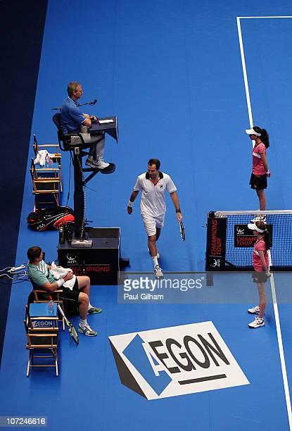 Greg Rusedski of Great Britain walks past Yevgeny Kafelnikov of Russia before serving during the match between Greg Rusedski and Yevgeny Kafelnikov...