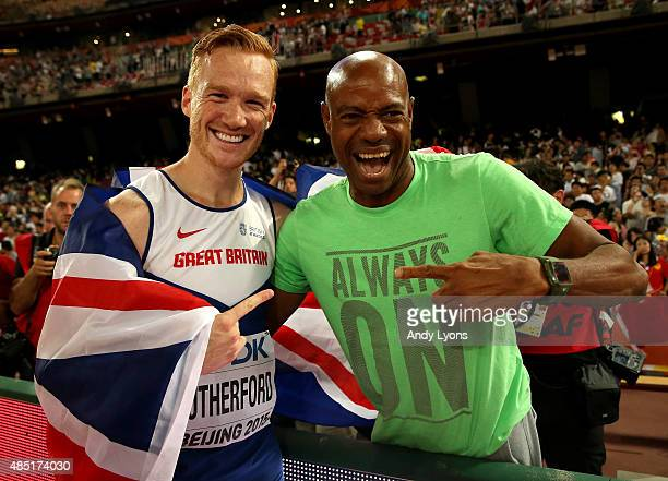 Greg Rutherford of Great Britain is congratulated by Mike Powell after winning gold in the Men's Long Jump final during day four of the 15th IAAF...