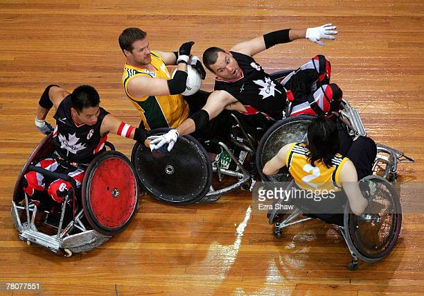 Greg Smith of Australia is defended by Ian Chan and Mike Whitehead of Canada during the 2007 Oceania Wheelchair Rugby Championships Final between...