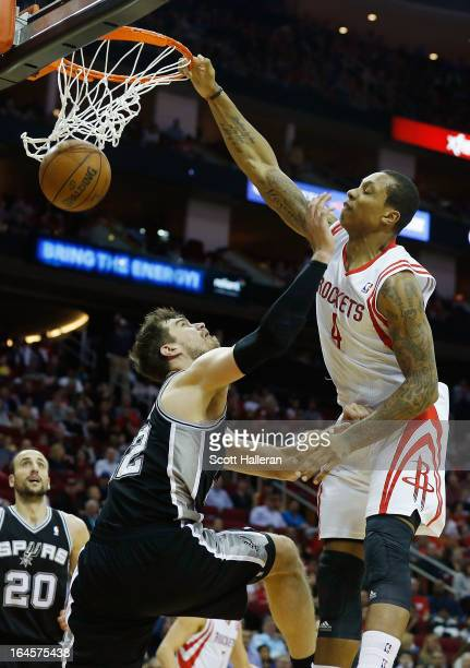 Greg Smith of the Houston Rockets dunks over Tiago Splitter of the San Antonio Spurs at Toyota Center on March 24 2013 in Houston Texas NOTE TO USER...