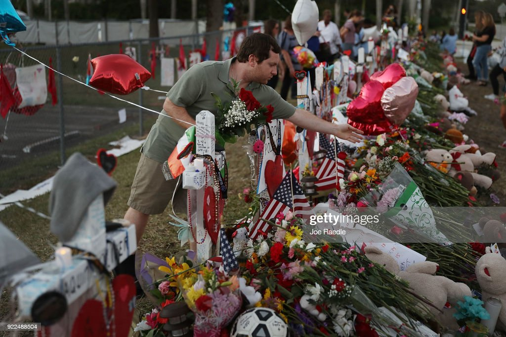 Greg Stein places flowers in a makeshift memorial setup in front of Marjory Stoneman Douglas High School in memory of the 17 people that were killed on February 14, on February 21, 2018 in Parkland, Florida. Police arrested 19-year-old former student Nikolas Cruz for killing 17 people at the high school.