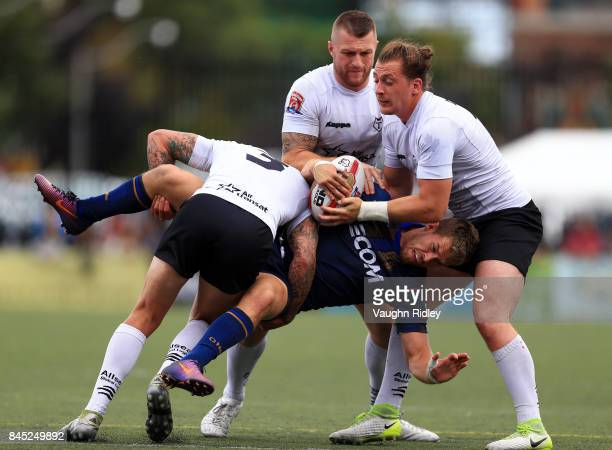 Greg Worthington and Andrew Dixon of Toronto Wolfpack tackle Tommy Holland of Whitehaven RLFC in the first half of a Kingstone Press League 1 Super...