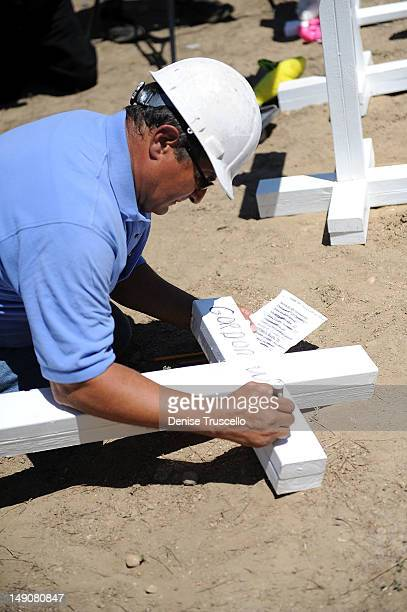 Greg Zanis from Aurora Ill places 12 white crosses in memoriam of the victims of Friday's shooting on July 22 2012 in Aurora Colorado Greg Zanis also...
