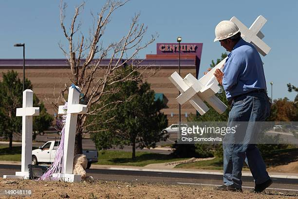 Greg Zanis of Aurora Illinois carries two of the twelve crosses he made for a makeshift memorial to the victims of last weekend's mass shooting at...