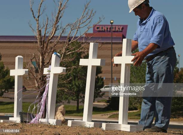 Greg Zanis of Aurora Illinois places two of the twelve crosses he made for a makeshift memorial to the victims of last weekend's mass shooting at the...